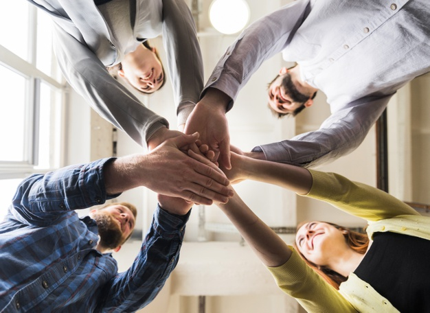 low-angle-view-businesspeople-stacking-hand-together-workplace_23-2148187232(1)